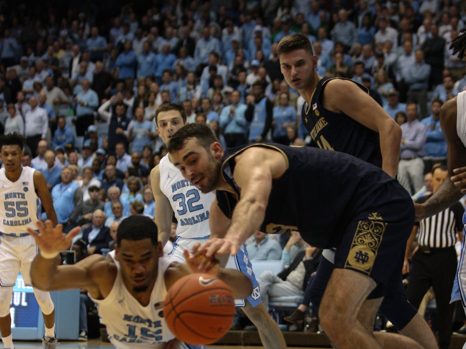 UNC forward Garrison Brooks (15) and Notre Dame forward John Mooney dive for the ball on Wednesday, Nov. 6, 2019 in the Dean E. Smith Center. The Tar Heels beat the Fighting Irish 76-65.