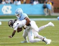 Defensive end Tomon Fox (12) tackles Western Carolina quarterback Tyrie Adams (12) on Saturday in Kenan Stadium.