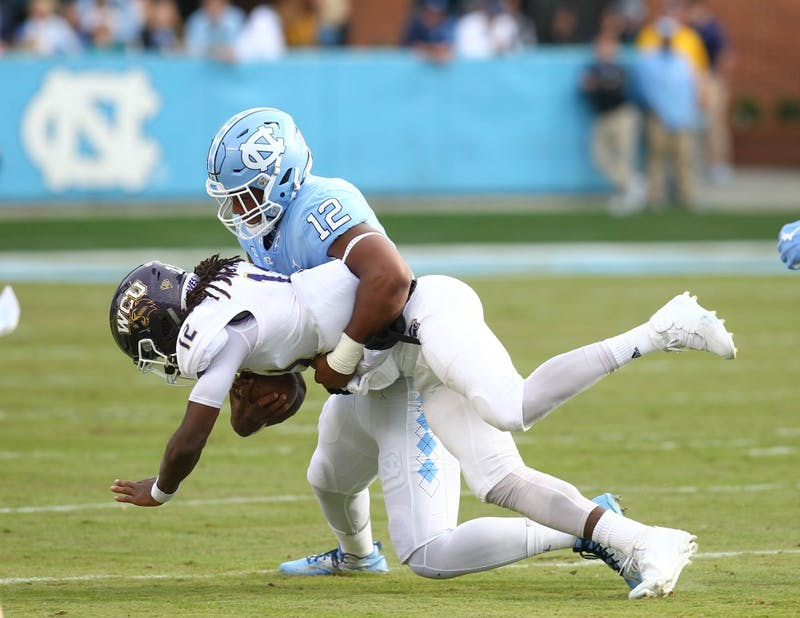 Defensive end Tomon Fox (12) tackles Western Carolina quarterback Tyrie Adams (12) on Saturday in Kenan Stadium.