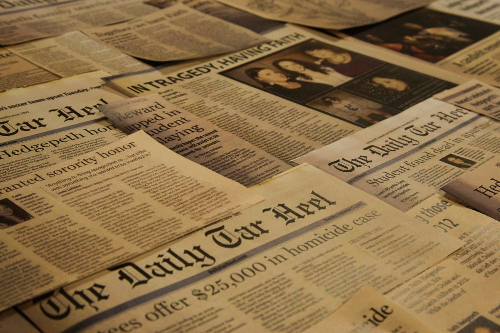 <p>DTH Photo illustration. Cutouts of old Daily Tar Heel articles about the unsolved murder of Faith Hedgepeth lay arranged on a table.</p>