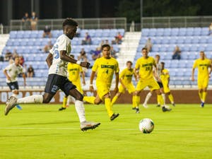 UNC senior forward Jelani Pieters (25) prepares for a kick with a looming UNCW team close by. The Tar Heels beat the Seahawks 2-0 at Dorrance Field on Tuesday, Oct. 1, 2019.