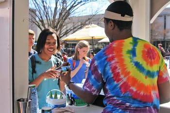 TJ Woodard (right), a junior economics major, serves Ben and Jerry's ice cream to Kady Forbes, a junior journalism and communications major.