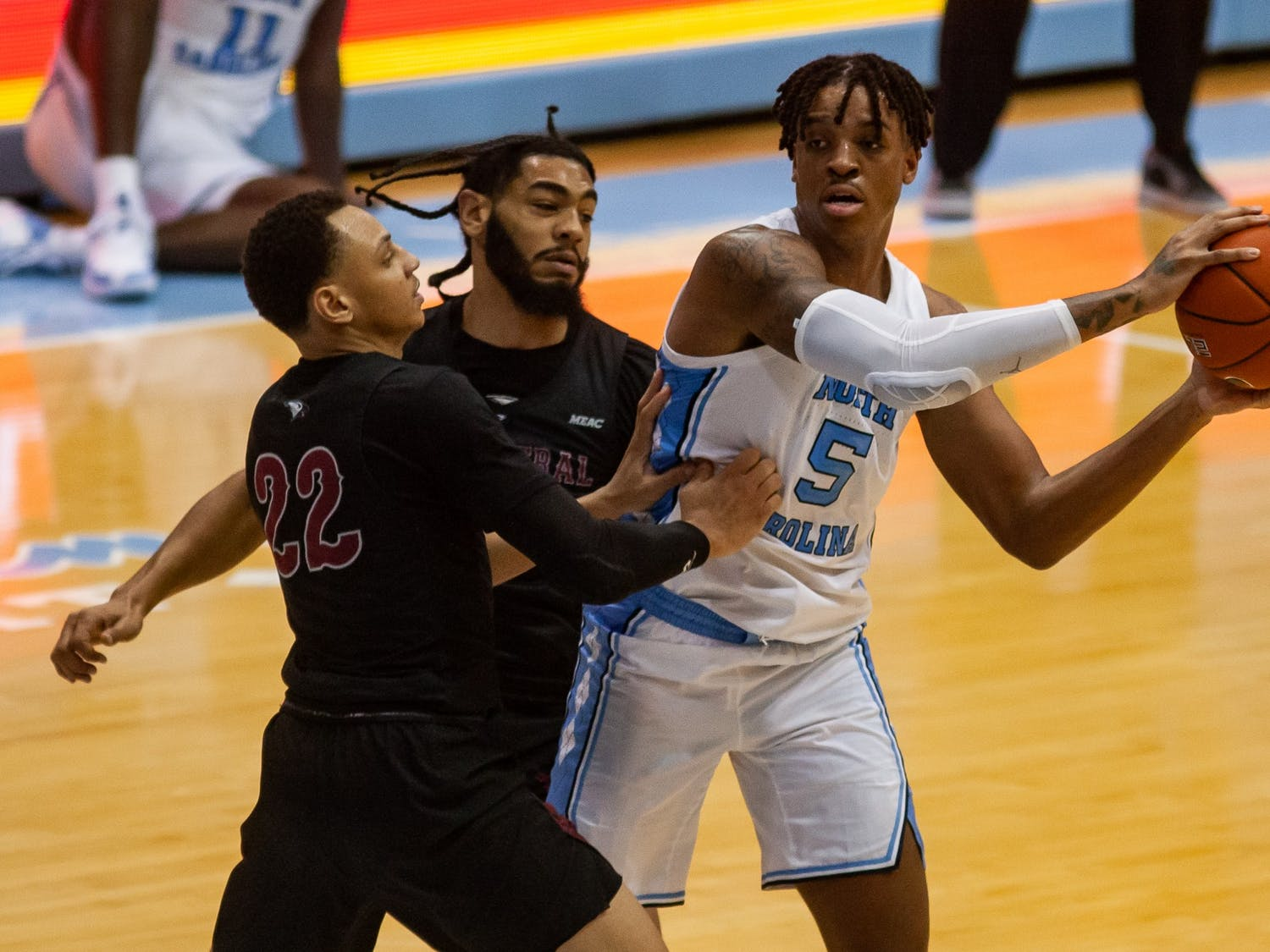 UNC sophomore center Armando Bacot (5) looks to make a pass around NCCU redshirt senior guard C.J. Keyser (22) and senior guard Deven Palmer (5) during a game in the Smith Center on Saturday, Dec. 12, 2020. UNC beat N.C. Central 73-67
