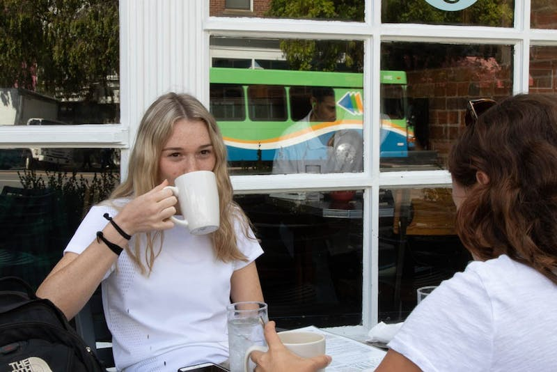 UNC first-year Alex Riginos, a peace, war, and defense major and Carly Terkiel, a sophomore psychology major, enjoy the weather with brunch at Carolina Coffee Shop on Thursday, Sept. 19 2019.