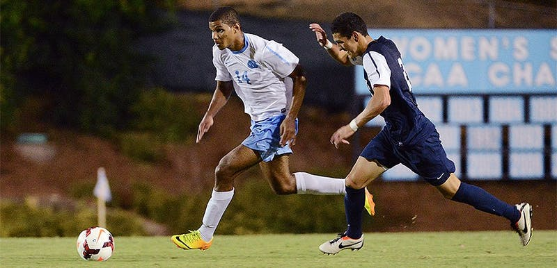 UNC midfielder Omar Holness (14) dribbles the ball up field as a Monmouth defender applies pressure.