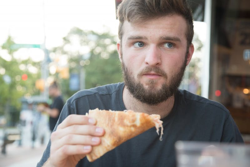 N.C. State Junior Mechanical Engineering major Justin Powers eats pizza at Italian Pizzeria III in Chapel Hill. Italian Pizzeria III is one of 9 pizza restaurants on Franklin Street.