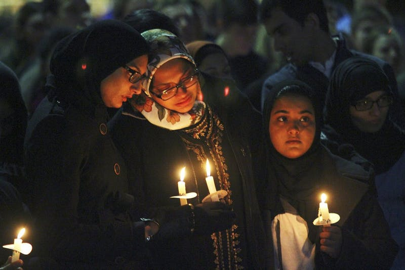 Mourners hold candles at a vigil in the Pit for Deah Shaddy Barakat, Yusor Mohammad Abu-Salha and Razan Mohammad Abu-Salha on Wednesday.