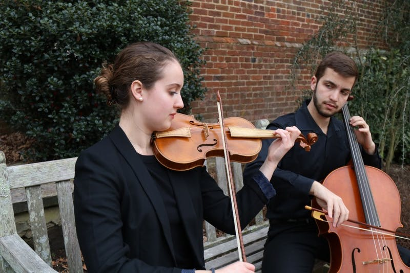 Emma Schubart (left), a sophomore music performance and political science major, and Daniel Malawsky (right), a junior biostatistics and mathematics major, play in front of Patterson Hall on Sunday, Feb. 3, 2019. Emma and Daniel are both part of the student orchestra of the opera at UNC.