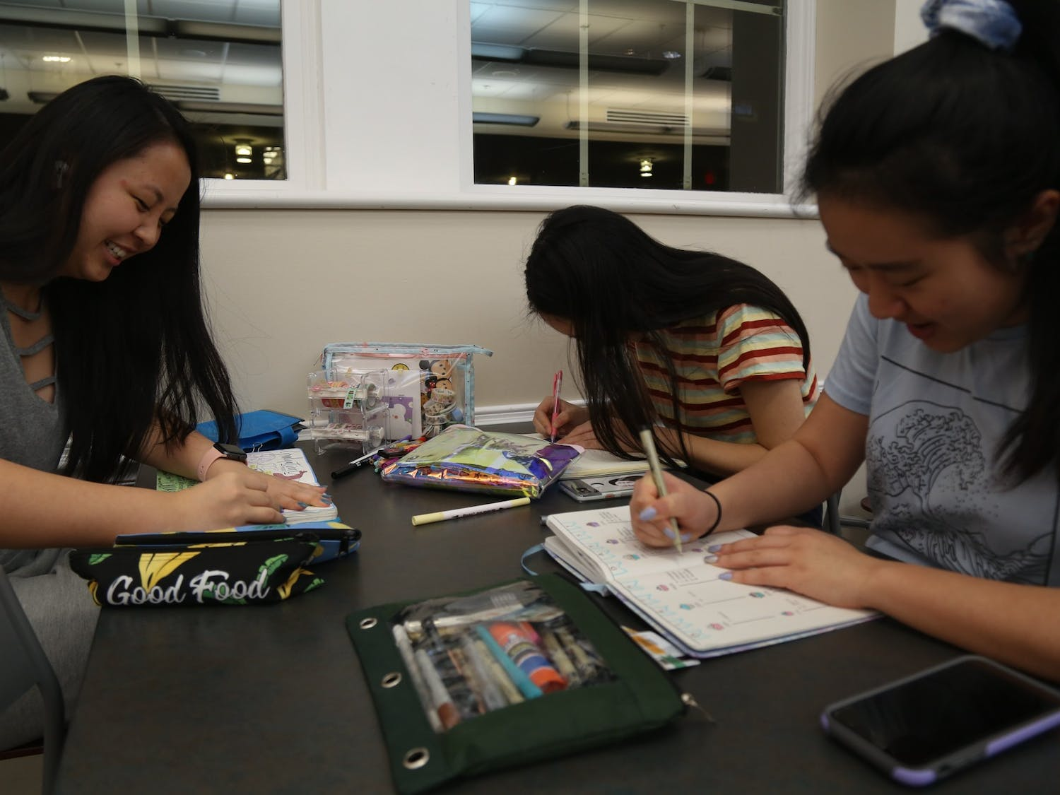 (From left) Jessie Zheng, first-year biology student, Claire Liang, first-year pre-nutrition student, and Liya Chen, first-year chemistry student work, on their bullet journals together in Lenoir Dining Hall at UNC-Chapel Hill on Monday, March 2, 2020.