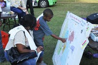 Andreah Williams and her son Tyshawn Pope look for their home on the community display at the Hargrove Community Center during the Good Neighbor Block Party on Tuesday afternoon.