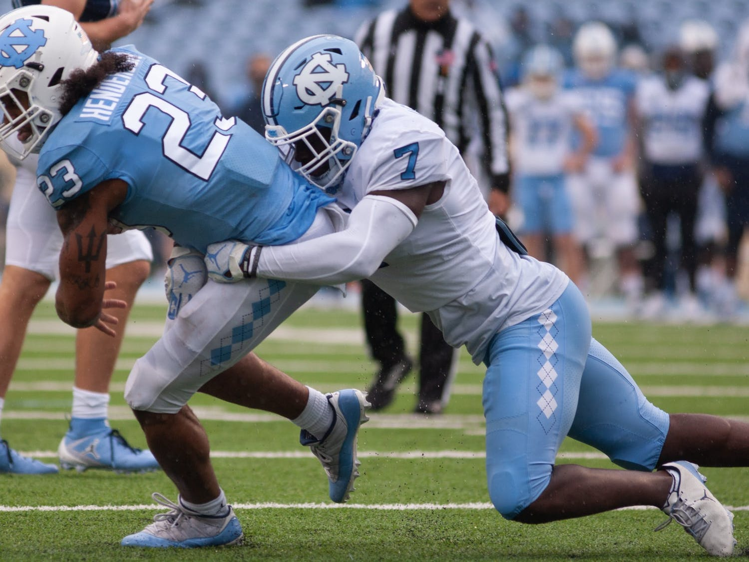 UNC junior linebacker Eugene Asante (7) tackles junior running back Josh Henderson (23) during Carolina's rainy spring game on April 24th in Kenan Stadium.