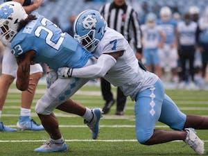UNC junior linebacker Eugene Asante (7) tackles junior running back Josh Henderson (23) during Carolina's rainy spring game on April 24th in Kenan Stadium.
