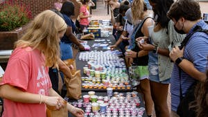 """Students select materials to make bracelets during Arts Everywhere's """"Fall Arts Pop-Up"""" in front of Davis Library on Sept. 16, 2021."""