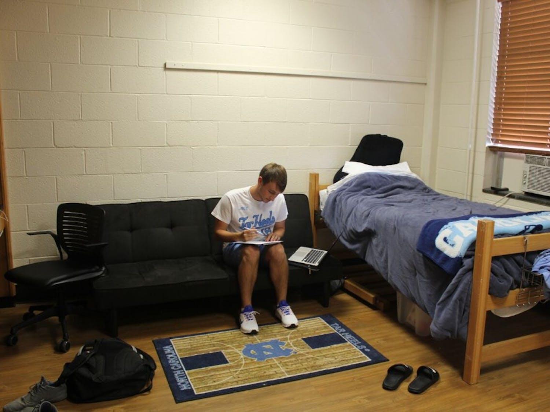 Resident Advisor Andrew Robinson, a junior biology major, works on homework in his room in Hinton James Residence Hall.