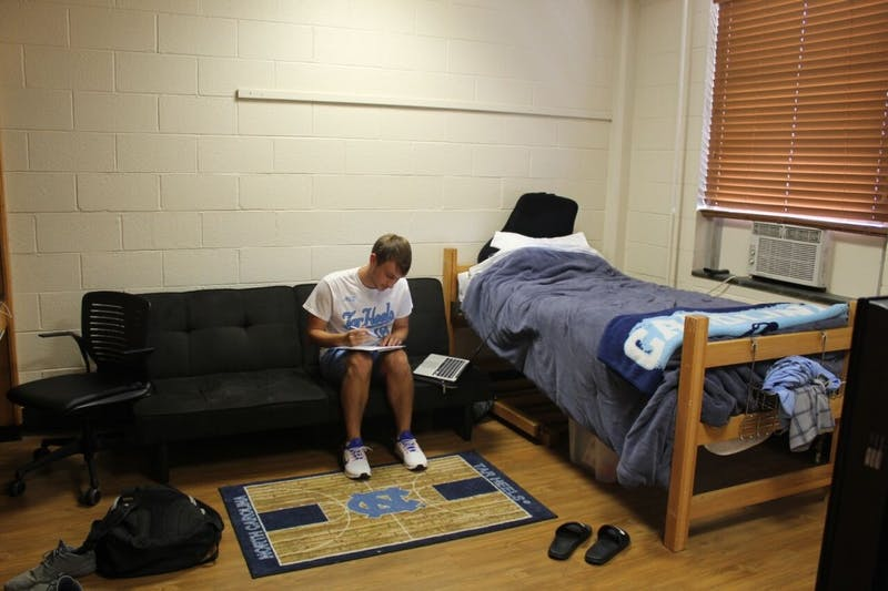 Resident Advisor Andrew Robinson, a junior biology major, works on homework in his room in Hinton James Residence Hall.