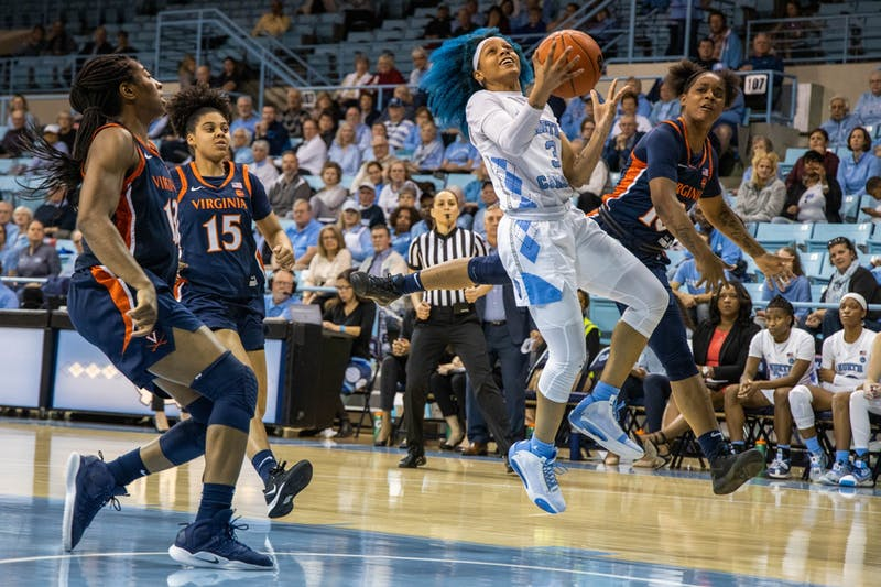 UNC redshirt senior guard Madinah Muhammed (3) aims for the hoop with University of Virginia first-year guard Shemera Williams (10) on defense. The Tar Heels beat the Cavaliers 78-68 in Carmichael Arena on Jan. 30, 2020.