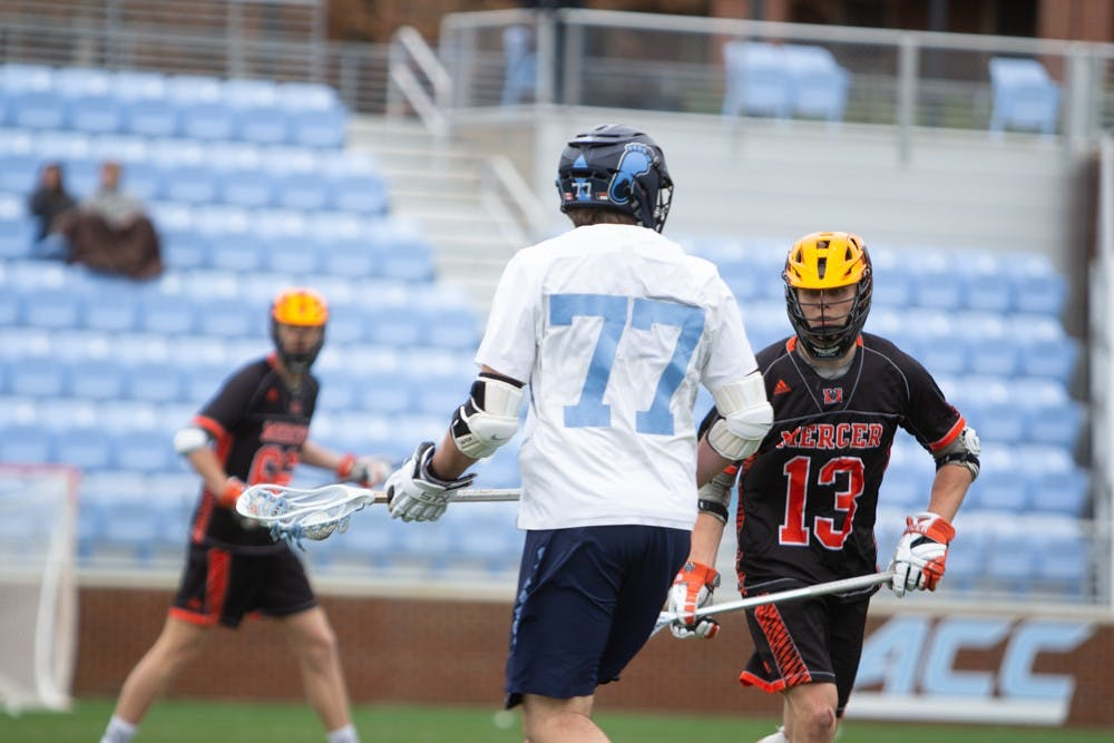 <p>Senior midfielder Tanner Cook (77) looks for a pass at Dorrance Field on Saturday, Feb. 8, 2020. UNC beat Mercer 14-6.</p>