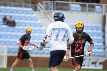 Senior midfielder Tanner Cook (77) looks for a pass at Dorrance Field on Saturday, Feb. 8, 2020. UNC beat Mercer 14-6.