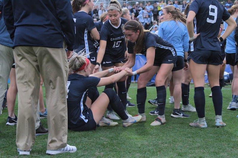 UNC senior, and tri-captain, Julia Ashley pulls Brigette Andrzejewski up after the team lost to FSU on Sunday during the National Championship game in Cary at WakeMed Soccer Park. UNC lost 0-1.