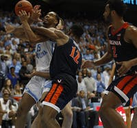 UNC sophomore forward Garrison Brooks (15) and Virginia redshirt sophomore guard De'Andre Hunter (12) fight for the ball on Monday, Feb. 11, 2019 in the Smith Center. UNC lost, 69-61.