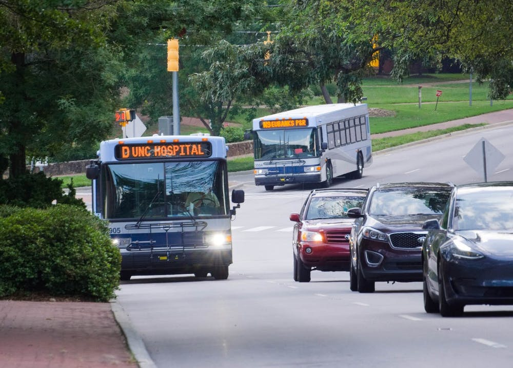 <p>Two Chapel Hill Transit buses, the D bus and NS bus, drive up South Columbia Street on Wednesday, Sept. 2, 2020.</p>