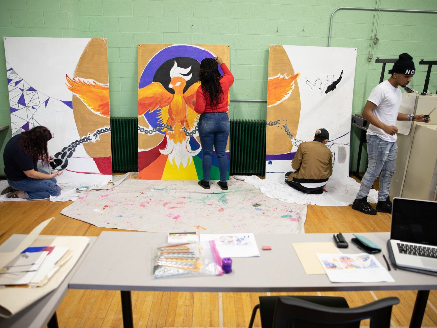 """(From left) Jenna Vaccarelli, Solea Merritt, Dakota Pesta and Stanley Rhodes work on Phoenix Academy's portion of a mural in the gymnasium on Thursday, Jan. 16, 2020, to be hung in the adjacent Lincoln Center. The Academy, the district's alternative school, prides itself on pushing students """"to learn, to succeed, and to lead."""""""