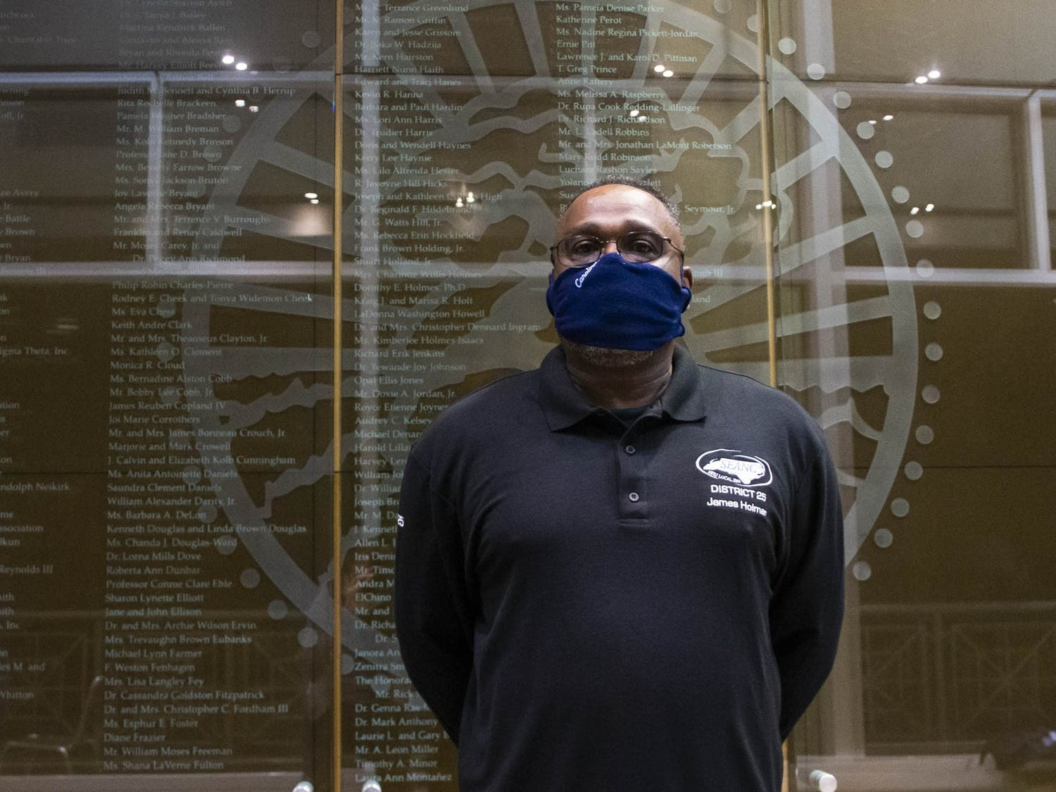 """James Holman, a crew leader for UNC housekeeping services and 15-year-long employee at the university, stands in front of a wall of honorable mentions in the Sonja Haynes Stone Center for Black Culture and History on Friday, October 16, 2020. Holman is the first recipient of the Rebecca Clark Staff Award for Moral Courage. Holman spoke about his role as a sort of liaison for his staff. """"I do a lot of advocacy work,"""" Holman said. He is the person that gets complaints heard and miscommunication straightened out, before it starts to affect people's work life and mental health. """"When the staff have issues, if it's a group issue, I will take it to the forum and then we'll take it tot the Vice Chancellors and try to get the situation resolved."""""""