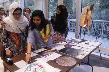 Soumaya Lansari (left), a junior global studies and sociology major, Ayesha Faisal (middle), a junior computer science major, and Safa Ahmed, a first-year media and journalism major look at art being auctioned at the Art and Welcoming Night on Tuesday. The proceeds from the auction will go to a fund for the victims of the Orlando shooting.