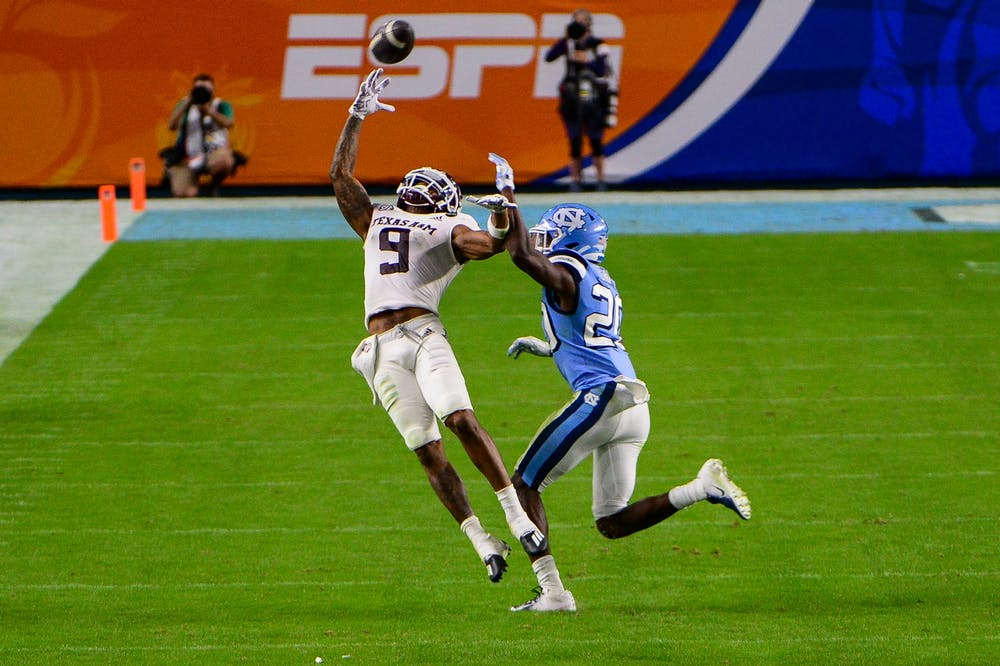 Texas A&M junior wide receiver Hezekiah Jones (9) attempts to catch the ball around UNC's first year defensive back Tony Grimes (20) during the Capital One Orange Bowl in Hard Rock Stadium on Saturday, Jan. 2, 2021. Texas A&M beat UNC 41-27.
