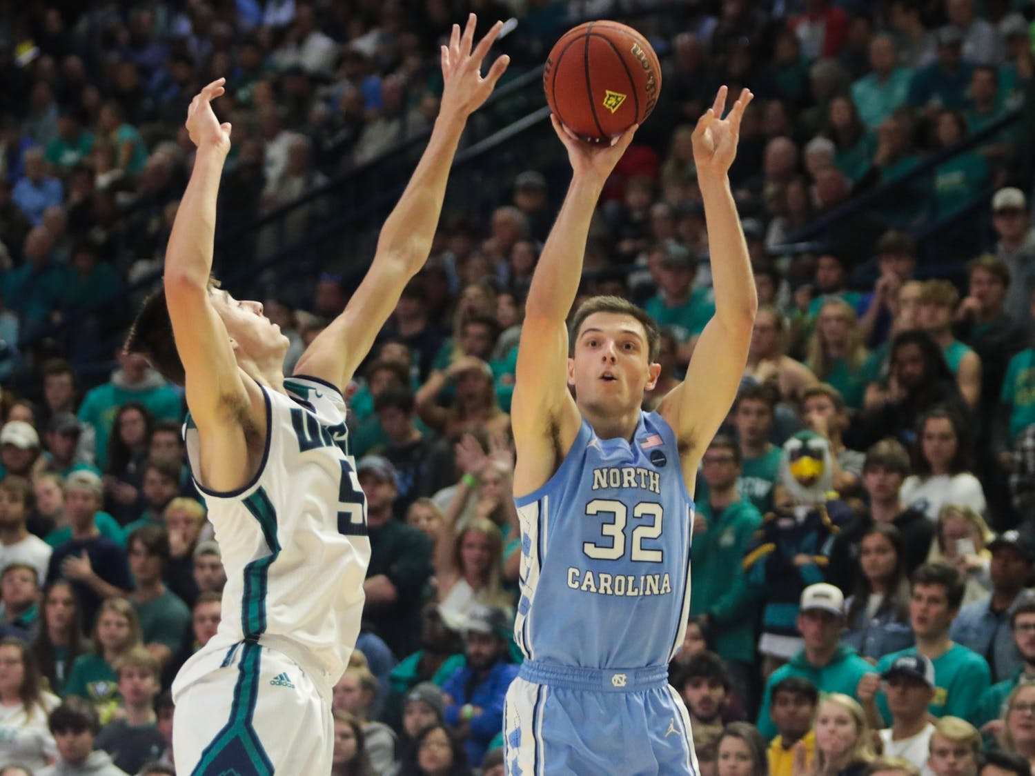 WCU freshman guard Jake Boggs (5) attempts to block as UNC graduate forward Justin Pierce (32) shoots the ball during their game at Trask Coliseum on Friday, Nov. 8, 2019. The Tar Heels beat the Seahawks 78-62.