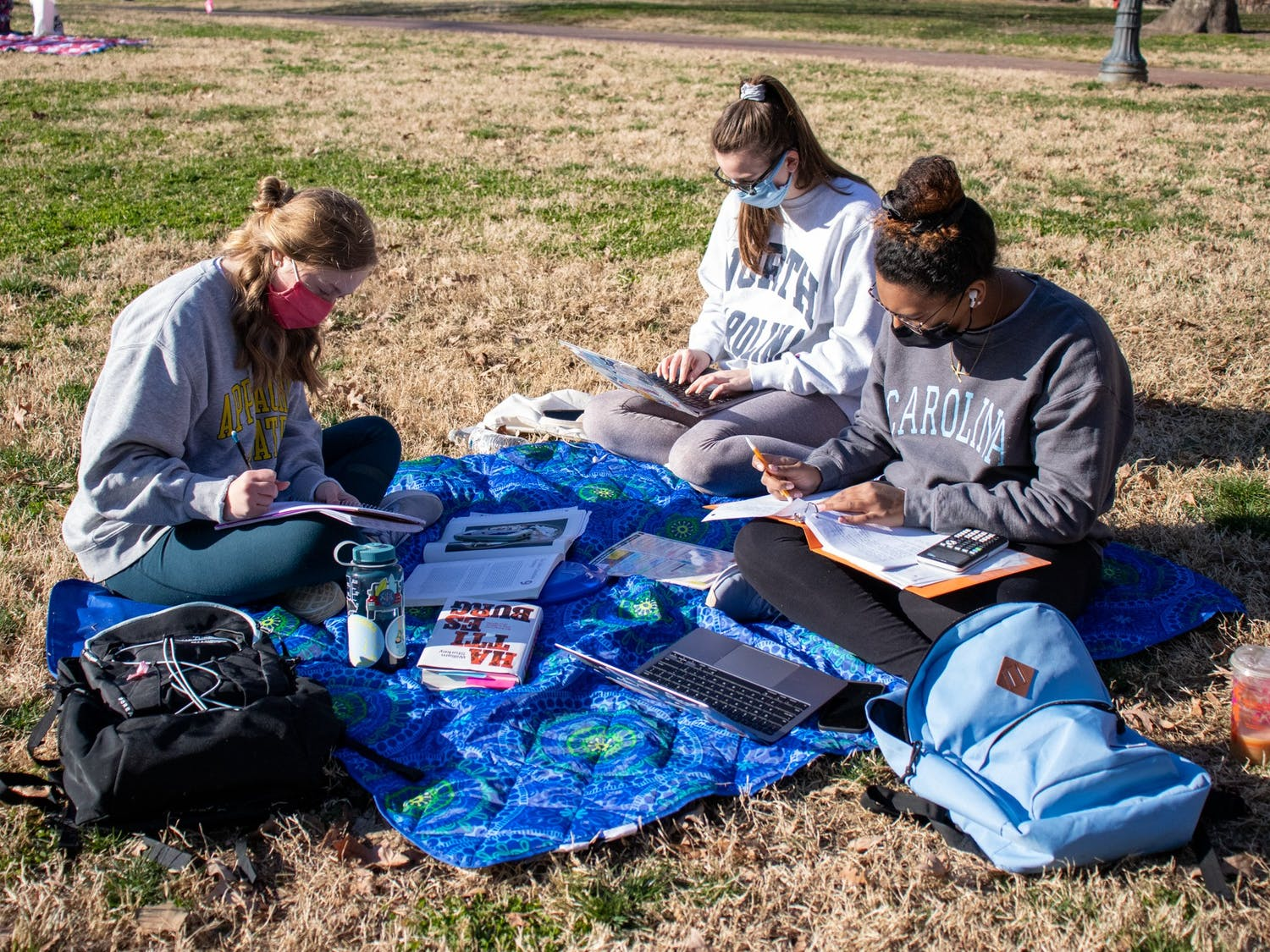 UNC students work on schoolwork at Polk Place in Chapel Hill on March 7, 2021.