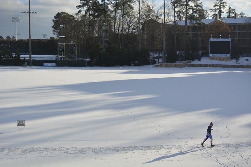 A runner circles the snow covered track around Fetzer Field on January 7th.