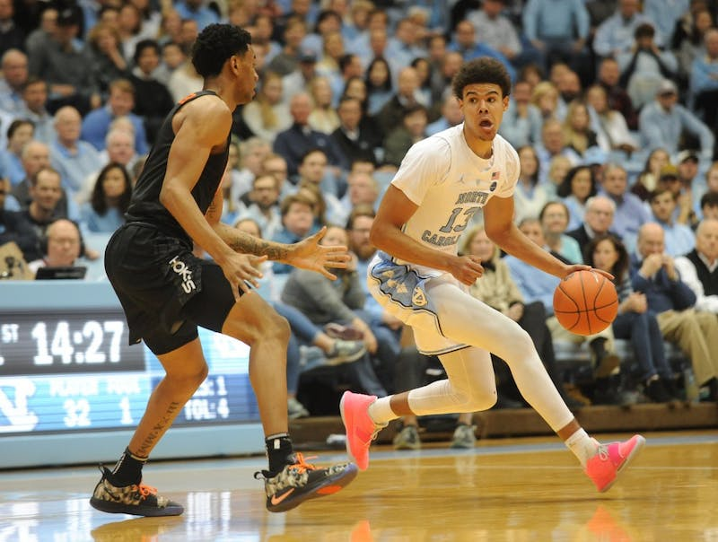 UNC graduate guard Cameron Johnson (13) evades Virginia Tech sophomore guard Nickeil Alexander-Walker (4) to make a pass at the Smith Center on Monday, Jan. 21, 2019. The Tar Heels won the game 103-82.