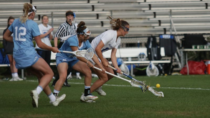 UNC midfielders, Ally Mastroianni (12) and Gianna Bowe (21), attempt to regain possession of the ball from Duke midfielder, Catriona Barry (19). No.3 UNC defeated No.13 Duke 19-5 on Saturday, April 20, 2019 at Koskinen Stadium at Duke University. UNC will enter the upcoming ACC Tournament as a No.2 seed.
