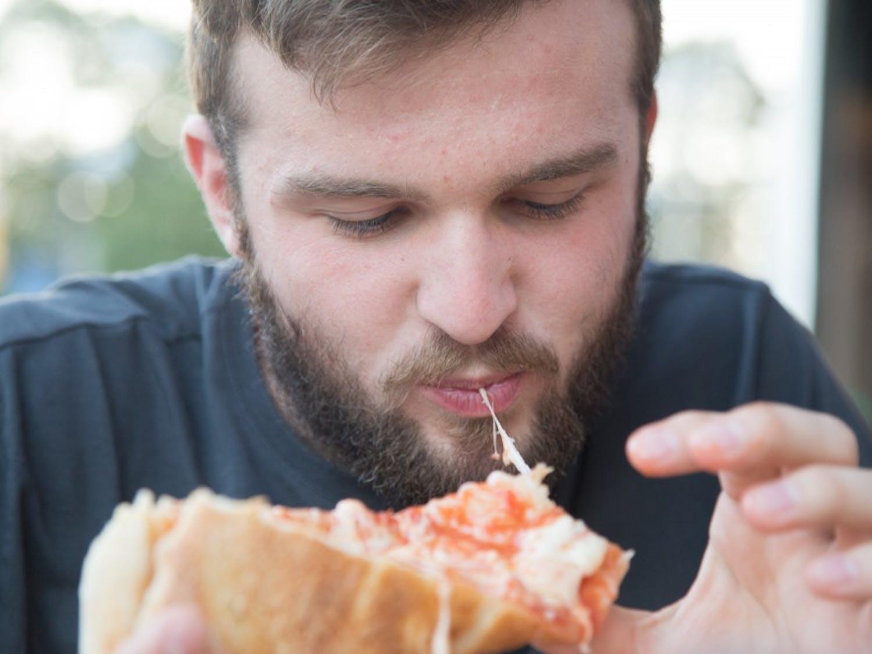 N.C. State Junior Mechanical Engineering major Justin Powers eats pizza at Italian Pizzeria III in Chapel Hill. Italian Pizzeria III is one of 9 pizza restaurants on Franklin Street.