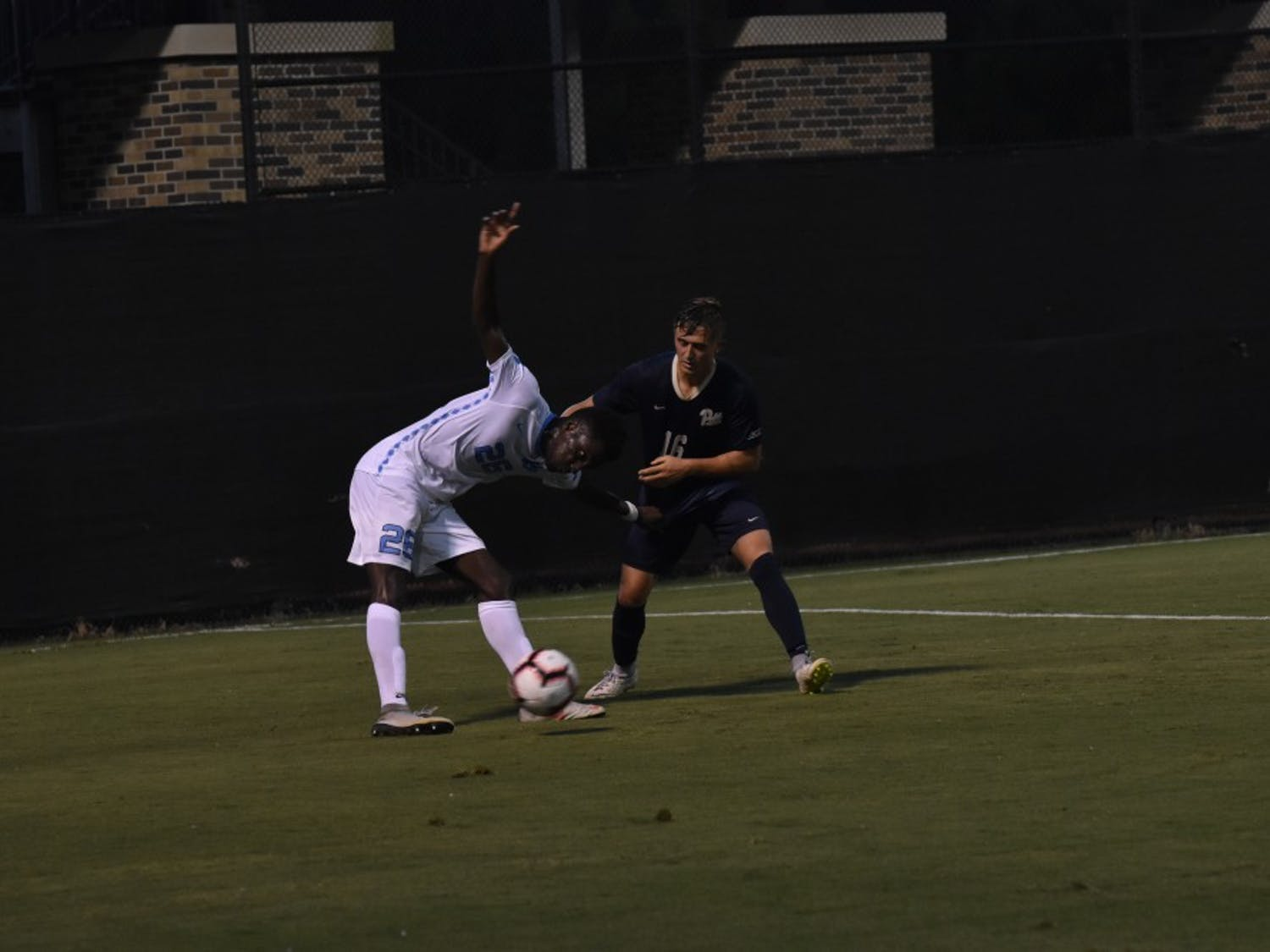 Forward Jelani Peiters (26) fights for the ball against defender Nyk Sessock (16) during Saturday night's game against Pittsburgh at Koskinen Stadium.