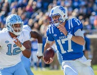 Duke quarterback Daniel Jones (17) outruns North Carolina defensive end Tomon Fox (12) at Wallace Wade Stadium on Nov. 10, 2018.