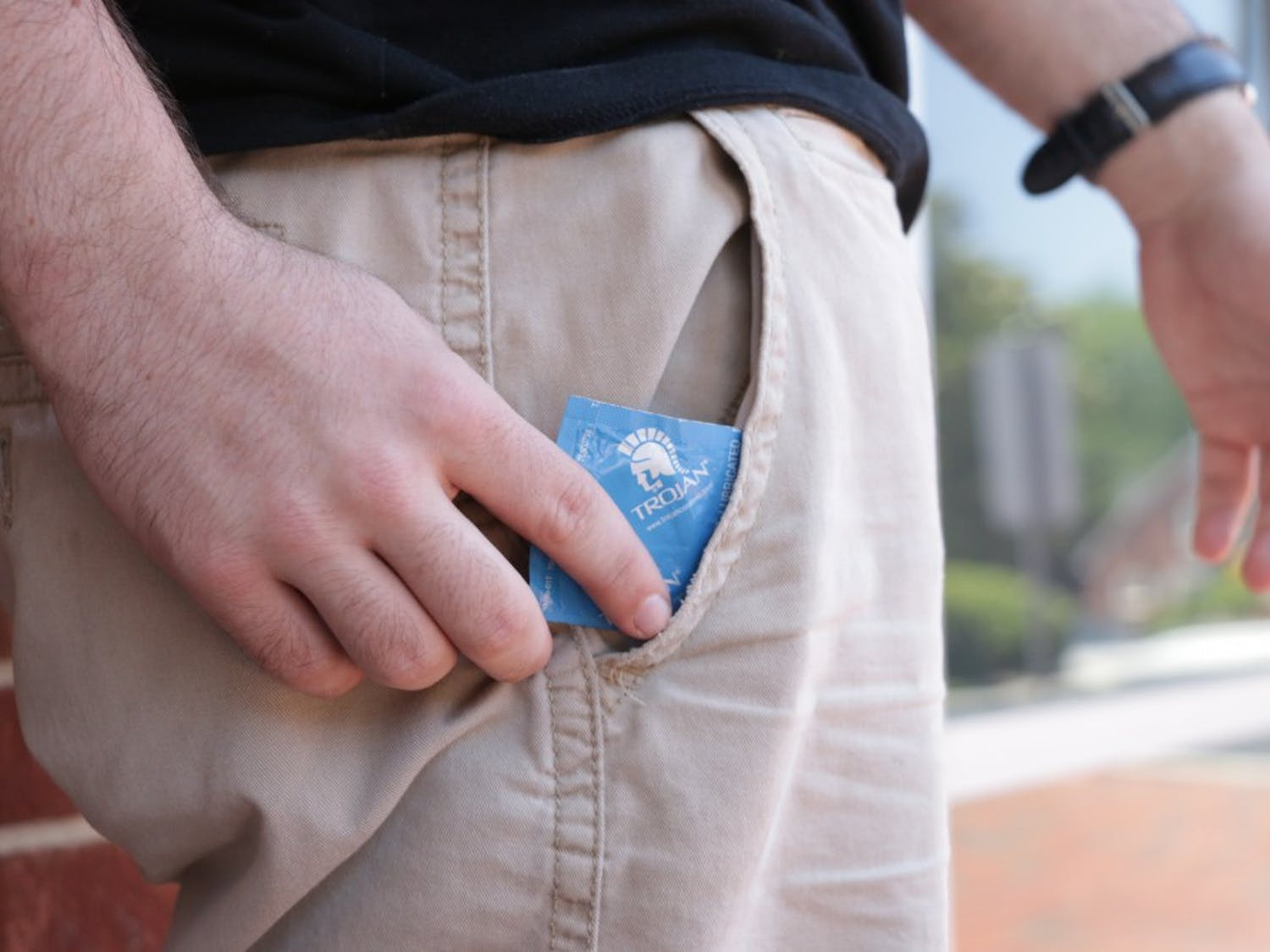 Photo illustration. A UNC student pulls a condom out of his pocket on Rosemary Street.