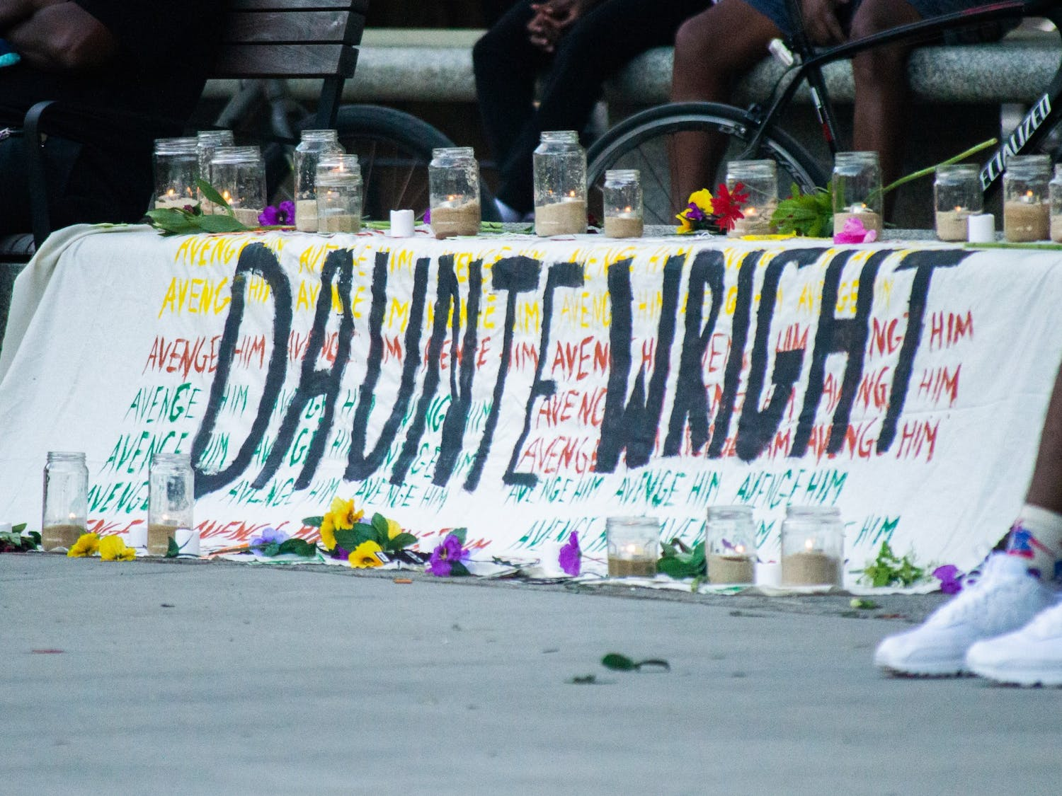 A banner with the words 'avenge him' written behind Daunte Wright's name sits at the front of a community organized vigil in memory of Daunte Wright and Jaida Peterson. The vigil took place in Moore Square Park in downtown Raleigh on Sunday Apr. 18, 2021.