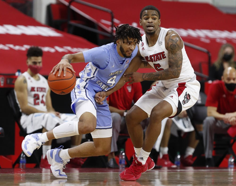 <p>R.J. Davis (4) drives around N.C. State's Thomas Allen (5) during the first half of N.C. State's game against UNC at PNC Arena in Raleigh, N.C., Tuesday, December 22, 2020. Carolina lost 79-76. Photo courtesy of Ethan Hyman</p>
