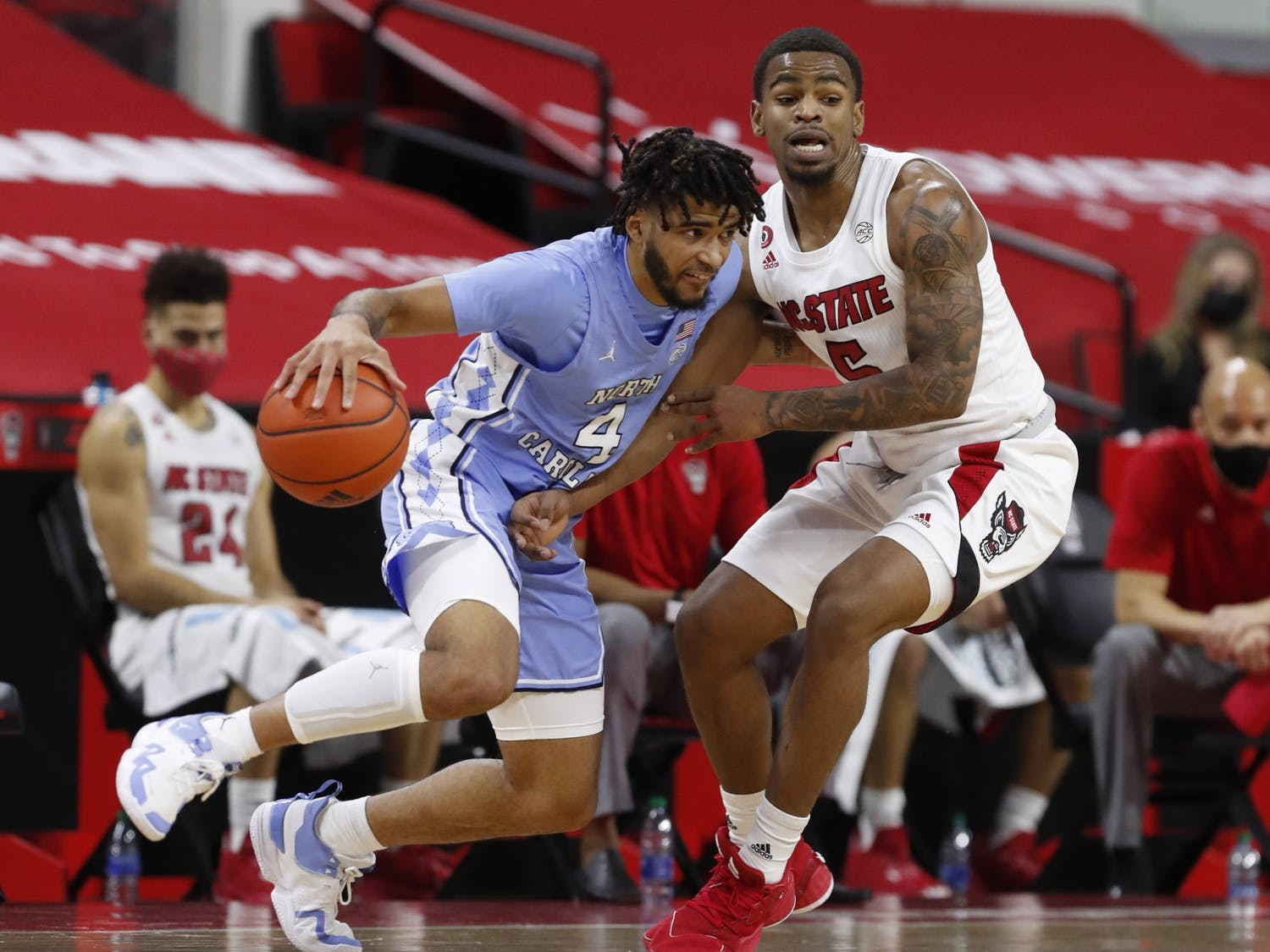 R.J. Davis (4) drives around N.C. State's Thomas Allen (5) during the first half of N.C. State's game against UNC at PNC Arena in Raleigh, N.C., Tuesday, December 22, 2020. Carolina lost 79-76. Photo courtesy of Ethan Hyman