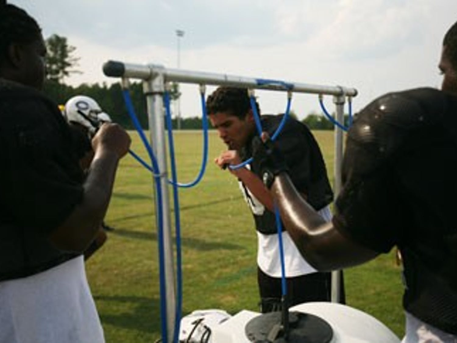 A Carrboro High School freshman, center, takes a break during a summer Thursday afternoon football practice.