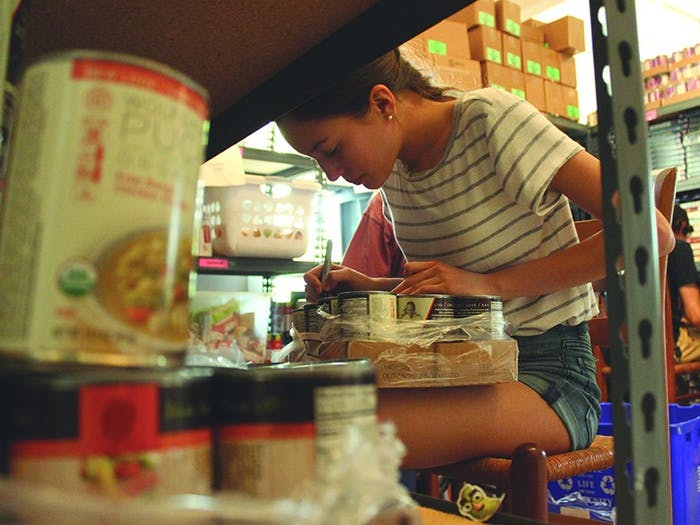 East Chapel Hill High School first year Nejma Hessini-Arandel writes dates on canned food donated to TABLE in Carrboro in May 2016.