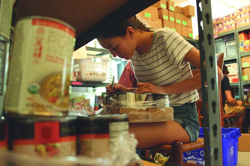 East Chapel Hill High School first year Nejma Hessini-Arandel writes dates on canned food donated to TABLE in Carrboro.