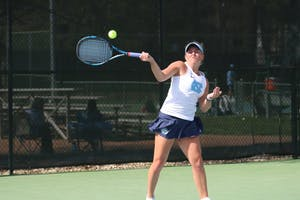 Makenna Jones follow through on a return shot against Virginia on April 13 at the Cone-Kenfield Tennis Center.