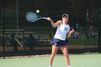 Makenna Jones follow through on a return shot against Virginia on April 13 at the Cone-Kenfield Tennis Center.