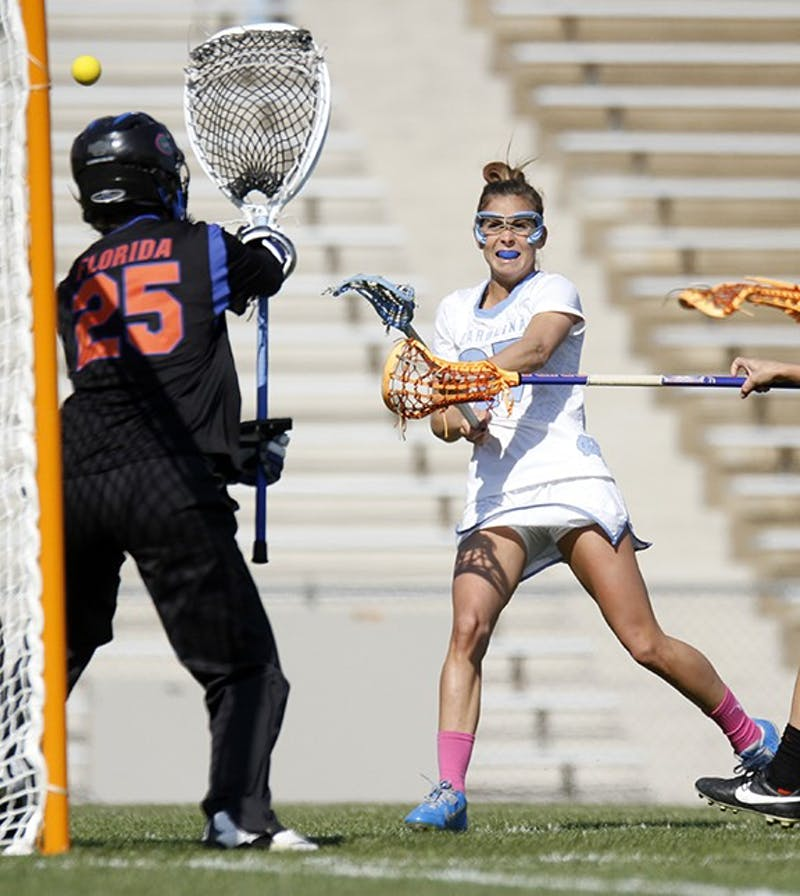 Aly Messinger (27) scores against Florida on Saturday. The Tar Heels won 20-8 at Fetzer Field.