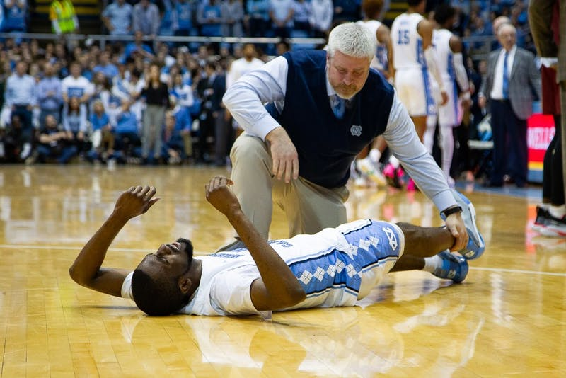 Doug Halverson, head athletic trainer for UNC men's basketball team, tends to UNC senior guard Brandon Robinson (4) after injury during a game against Boston College on in the Smith Center on Saturday, Feb. 1, 2020.