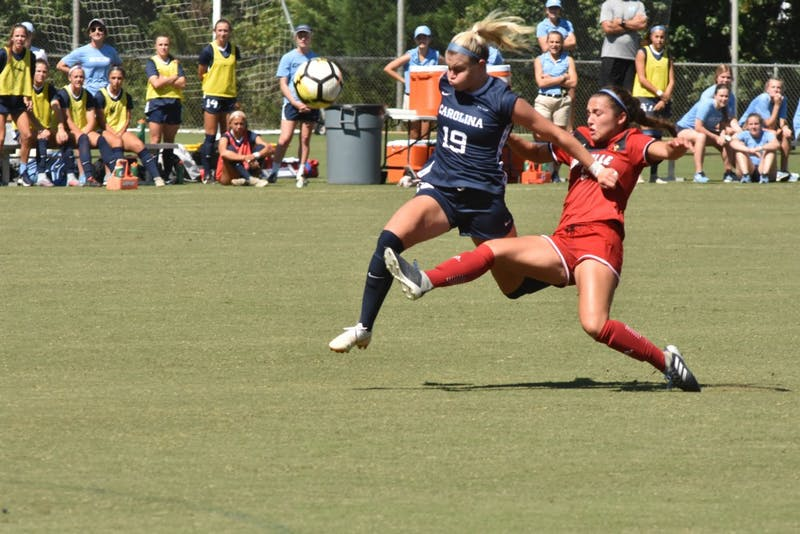 UNC Sophomore Forward Alessia Russo (19) dribbles past Freshman Louisville Defender Sarah Hernandez during Saturday's game against Louisville at WakeMed Soccer Park. UNC won 5-1