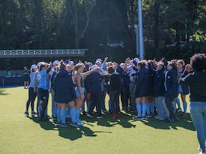 The field hockey team gathers and cheers as part of the celebration for seniors following their 5-2 win over Duke.